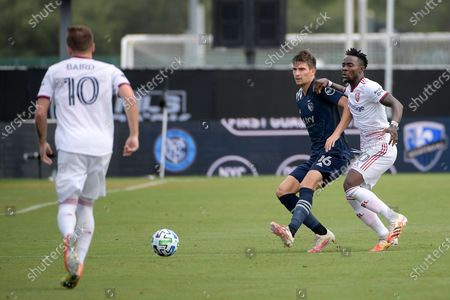 Sporting Kansas City midfielder Graham Smith (16) passes a ball between Real Salt Lake forward Sam Johnson (50) and forward Corey Baird (10) during the first half of an MLS soccer match, in Kissimmee, Fla