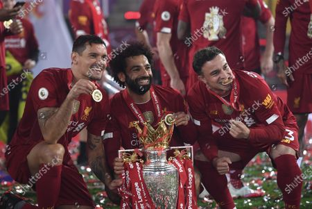 Liverpool's Dejan Lovren, Mohamed Salah and Liverpool's Xherdan Shaqiri, from left, celebrate with the English Premier League trophy after it was presented following the Premier League soccer match between Liverpool and Chelsea at Anfield stadium in Liverpool, England