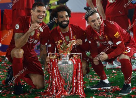 Liverpool's Mohamed Salah, ceter, and Liverpool's Xherdan Shaqiri, right, and Liverpool's Dejan Lovren pose with the English Premier League trophy following its presentation after the English Premier League soccer match between Liverpool and Chelsea at Anfield Stadium in Liverpool, England, . Liverpool are champions of the EPL for the season 2019-2020. The trophy is presented at the teams last home game of the season. Liverpool won the match against Chelsea 5-3