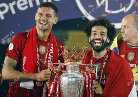 Liverpool's Dejan Lovren (L) and Mohamed Salah celebrate the Premier League title following the English Premier League soccer match between Liverpool FC and Chelsea FC in Liverpool, Britain, 22 July 2020.