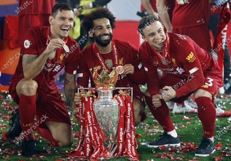 (L-R) Liverpool's Dejan Lovren, Mohamed Salah and Xherdan Shaqiri pose with the Premier League trophy following the English Premier League soccer match between Liverpool FC and Chelsea FC in Liverpool, Britain, 22 July 2020.