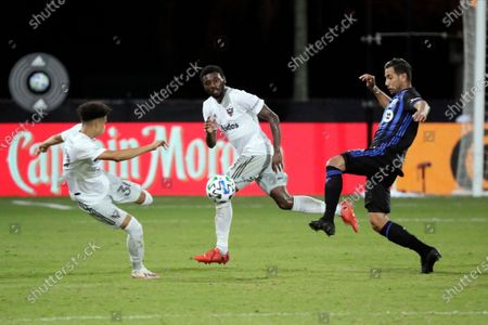Stock Photo of United midfielder Kevin Paredes, left, and Montreal Impact midfielder Saphir Taider, right, battle for possession as D.C. United defender Chris Odoi-Atsem, center, looks on during the second half of an MLS soccer match, in Kissimmee, Fla