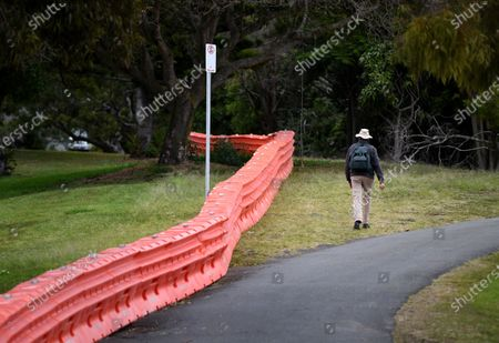 A man walks on the Queensland (QLD) side of a separation barrier dividing a park on the Queensland-New South Wales border in Coolangatta, Queensland,  Australia, 23 July 2020. The barrier was built in a police push to stop illegal border crossings from New South Wales (NSW). Queensland Premier Annastacia Palaszczuk said the state government is considering declaring more NSW postcodes hotspots.