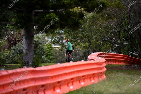 A cyclist rides on the New South Wales side of a separation barrier dividing a park on the Queensland-New South Wales border in Coolangatta, Queensland,  Australia, 23 July 2020. The barrier was built in a police push to stop illegal border crossings from New South Wales (NSW). Queensland Premier Annastacia Palaszczuk said the state government is considering declaring more NSW postcodes hotspots.