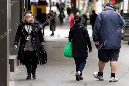 A woman is seen walking in the CBD as she wears a full face shield in Melbourne as the Victorian Premier confirmed 403 new coronavirus cases overnight. As of 11.59pm on Wednesday 22 July, people living in metropolitan Melbourne and Mitchell Shire and will now be required to wear a face covering when leaving home, following a concerning increase in coronavirus cases in recent days. The fine for not wearing a face covering will be $200.