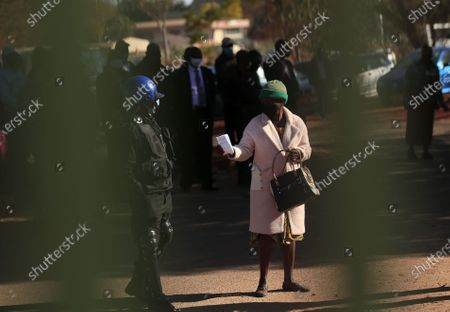 A police officer checks a pedestrian's pass permit in Harare, Zimbabwe, on July 22, 2020. Zimbabwean President Emmerson Mnangagwa on Tuesday announced a raft of more strict lockdown measures including imposing a curfew from 6 pm to 6 am to curb rising cases of COVID-19.