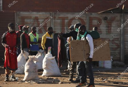 People wait for hitchhiking at a bus station in Harare, Zimbabwe, on July 22, 2020. Zimbabwean President Emmerson Mnangagwa on Tuesday announced a raft of more strict lockdown measures including imposing a curfew from 6 pm to 6 am to curb rising cases of COVID-19.