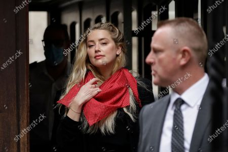 """American actress Amber Heard waves at the media as she arrives at the High Court in London, . Actor Johnny Depp is suing News Group Newspapers, publisher of The Sun, and the paper's executive editor, Dan Wootton, over an April 2018 article that called him a """"wife-beater."""" Depp strongly denies all allegations"""