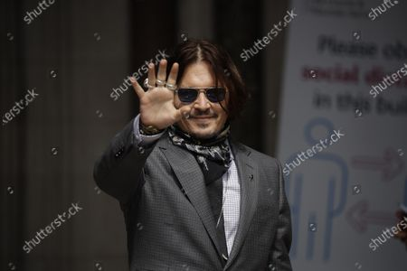 """Actor Johnny Depp turns round and waves at fans and the media as he arrives at the High Court in London, . Actor Johnny Depp is suing News Group Newspapers, publisher of The Sun, and the paper's executive editor, Dan Wootton, over an April 2018 article that called him a """"wife-beater."""" Depp strongly denies all allegations"""
