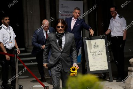 """Stock Picture of Actor Johnny Depp turns round and walks back to receive a gift of flowers from a fan as he arrives at the High Court in London, . Actor Johnny Depp is suing News Group Newspapers, publisher of The Sun, and the paper's executive editor, Dan Wootton, over an April 2018 article that called him a """"wife-beater."""" Depp strongly denies all allegations"""