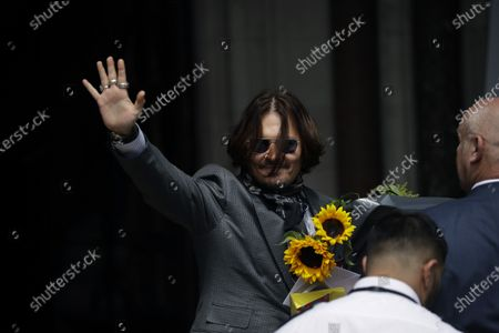 """Actor Johnny Depp turns round and waves at fans and the media as he arrives at the High Court in London, . Depp is suing News Group Newspapers, publisher of The Sun, and the paper's executive editor, Dan Wootton, over an April 2018 article that called him a """"wife-beater."""" The Sun's defense relies on a total of 14 allegations by Heard of Depp's violence. He strongly denies all of them"""