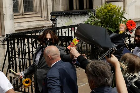 """Stock Image of Actor Johnny Depp turns to receive a gift from a fan as he arrives at the High Court in London, . Depp is suing News Group Newspapers, publisher of The Sun, and the paper's executive editor, Dan Wootton, over an April 2018 article that called him a """"wife-beater."""" The Sun's defense relies on a total of 14 allegations by Heard of Depp's violence. He strongly denies all of them"""