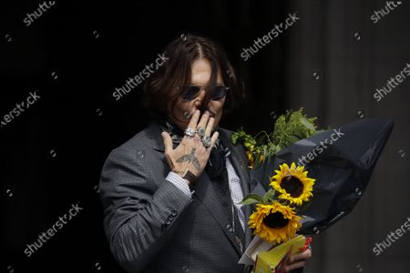 """Actor Johnny Depp blows a kiss to fans as he turns round holding flowers and gifts they gave him as he arrives at the High Court in London, . Depp is suing News Group Newspapers, publisher of The Sun, and the paper's executive editor, Dan Wootton, over an April 2018 article that called him a """"wife-beater."""" The Sun's defense relies on a total of 14 allegations by Heard of Depp's violence. He strongly denies all of them"""