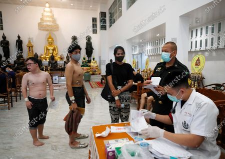 Thai transgender Aticha Choimsri (2-R) and other men line up for health check during military conscription in Bangkok, Thailand, 23 July 2020. The Royal Thai Armed Forces launched their annual military conscription draft day, searching for healthy men of fighting age from 21 years old, while transgender women who have a body not consistent with their birth sex and have undergone breast augmentation surgery and full gender reassignment operations are exempted from military service. Approximately 100,000 Thai men are drafted annually.