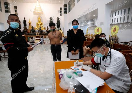 Thai transgender Boonyarit Dulsungnern (R) and a man line up for health check during military conscription in Bangkok, Thailand, 23 July 2020. The Royal Thai Armed Forces launched their annual military conscription draft day, searching for healthy men of fighting age from 21 years old, while transgender women who have a body not consistent with their birth sex and have undergone breast augmentation surgery and full gender reassignment operations are exempted from military service. Approximately 100,000 Thai men are drafted annually.