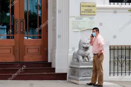 A man makes a call outside the entrance of the Chinese consulate in San Francisco, California, USA, 23 July 2020. The FBI alleges that a biology researcher linked to the Chinese military is taking refuge in the Chinese consulate to avoid getting arrested for visa fraud.