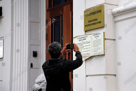 A mann takes a picture of the Chinese consulate sign in San Francisco, California, USA, 23 July 2020. The FBI alleges that a biology researcher linked to the Chinese military is taking refuge in the Chinese consulate to avoid getting arrested for visa fraud.