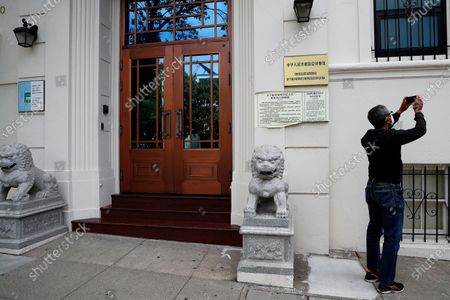 A person takes picture outside the Chinese consulate in San Francisco, California, USA, 23 July 2020. The FBI alleges that a biology researcher linked to the Chinese military is taking refuge in the Chinese consulate to avoid getting arrested for visa fraud.