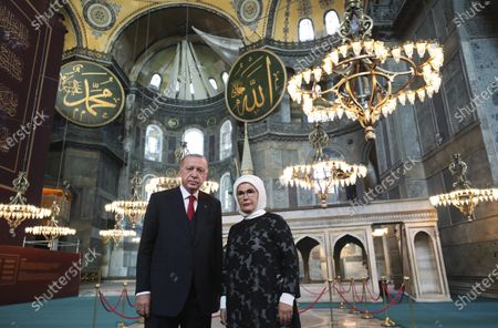 """Turkey's President Recep Tayyip Erdogan, accompanied by his wife Emine, poses for photographs as he visits the Byzantine-era Hagia Sophia, in the historic Sultanahmet district of Istanbul, a day before the first Muslim prayers in the monument in 86 years following its conversion back into a mosque. The conversion of the edifice, once the most important church of Christendom and the """"jewel"""" of the Byzantine Empire, has led to an international outcry"""