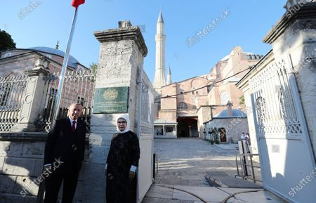 """Turkey's President Recep Tayyip Erdogan, accompanied by his wife Emine, poses for photographs after the unveiling of a sign at the entrance of the Byzantine-era Hagia Sophiat that reads: """"The Hagia Sophia Grand Mosque"""" in the historic Sultanahmet district of Istanbul, a day before the first Muslim prayers in the monument in 86 years following its conversion back into a mosque. The conversion of the edifice, once the most important church of Christendom and the """"jewel"""" of the Byzantine Empire, has led to an international outcry"""