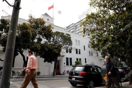 Pedestrians walk across the street to the Chinese consulate in San Francisco, California, USA, 23 July 2020. The FBI alleges that a biology researcher linked to the the Chinese military is taking refuge in the Chinese consulate to avoid getting arrested for visa fraud.