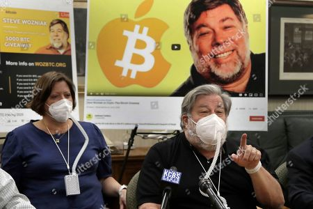 Stock Photo of Apple co-founder Steve Wozniak, right, gestures beside his wife Janet Hill during a media conference, in Burlingame, Calif. Wozniak is launching a legal attack against Google's YouTube video site for allowing con artists to use him as a pawn in a Bitcoin scam believed to have heisted millions of dollars from people around the world