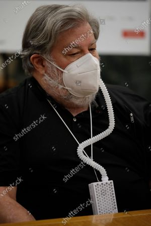 Apple co-founder Steve Wozniak wears an air filtration system during a media conference, in Burlingame, Calif. Wozniak is joining a legal fight taking aim at the flimsy controls on Google's YouTube video site that have turned him into a unwilling pawn in a scam that has stolen millions of dollars from people around the world