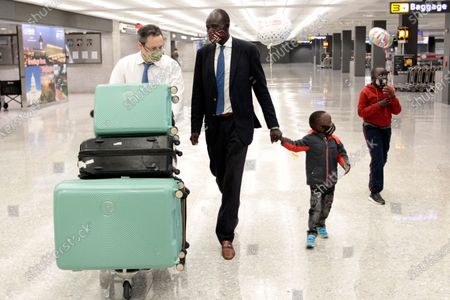 Stock Image of Peter Biar Ajak, center, walks with Baraka Ajak, Deng Ajak and his lawyer Jared Genser, left, upon his arrival at Washington Dulles International Airport in Chantilly, Va