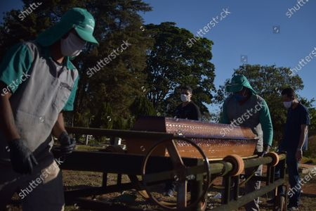 Julio Cesar Ramos (C) and his cousin Eduardo Magela (R) attend the funeral of Ivanilde Maria das Dores, Ramos' mother, who died after contracting COVID-19, at Campo da Esperanca Cemetery in Brasilia, Brazil, 23 July 2020. Although authorities insist that the infection curve is stabilized in Brazil, the number of infections remains on the rise.