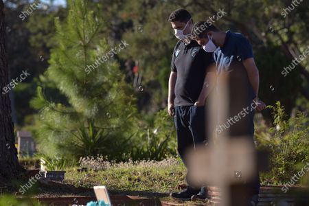 Julio Cesar Ramos (L) and his cousin Eduardo Magela (R) attend the funeral of Ivanilde Maria das Dores, Ramos' mother, who died after contracting COVID-19, at Campo da Esperanca Cemetery in Brasilia, Brazil, 23 July 2020. Although authorities insist that the infection curve is stabilized in Brazil, the number of infections remains on the rise.