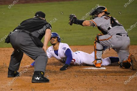Los Angeles Dodgers' Mookie Betts, center, scores on a fielder's choice hit by Justin Turner as San Francisco Giants catcher Tyler Heineman takes a late throw and home plate umpire Bill Miller makes the call during the seventh inning of an opening day baseball game, in Los Angeles