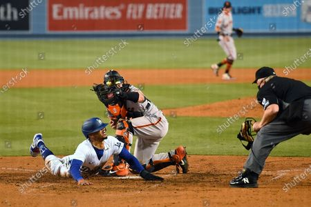 Los Angeles Dodgers' Mookie Betts, left, scores on a fielder's choice hit by Justin Turner as San Francisco Giants catcher Tyler Heineman takes a late throw and home plate umpire Bill Miller makes the call during the seventh inning of an opening day baseball game, in Los Angeles