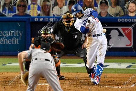 Los Angeles Dodgers' Mookie Betts, right, hits a single as San Francisco Giants relief pitcher Tyler Rogers, foreground, watches along with catcher Tyler Heineman and home plate umpire Bill Miller during the seventh inning of an opening day baseball game, in Los Angeles