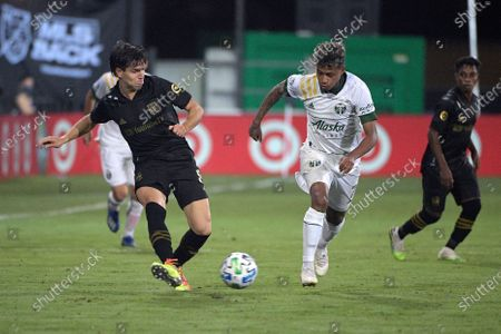 Los Angeles FC midfielder Francisco Ginella (8) passes the ball in front of Portland Timbers forward Andy Polo (7) during the second half of an MLS soccer match, in Kissimmee, Fla