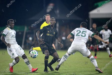 Los Angeles FC forward Bradley Wright-Phillips, center, passes the ball between Portland Timbers midfielder Diego Chara (21) and defender Bill Tuiloma (25) during the second half of an MLS soccer match, in Kissimmee, Fla