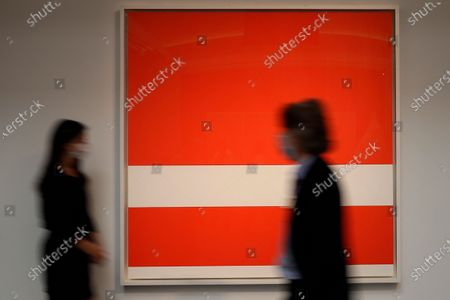 Stock Image of People walk past a painting by Ellsworth Kelly called 'Red White' at Sotheby's auction rooms in London, . The painting estimated at 1.8-2.5 million UK Pounds (2.3-3.19 million US Dollars) will go on sale in the 'Rembrandt to Richter' evening sale on July 28