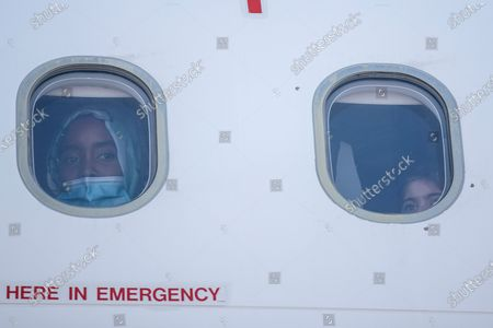 Young woman and a child look out of a window of a plane as group of 85 migrant children with health issues board a plane to Germany, at Athens International Airport, . German Foreign Heiko Maas, on a visit to Athens this week, said his country would follow through in its pledge to assist Greece with the relocation of unaccompanied minors and other children at refugee camps in Greece