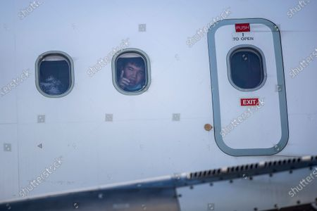 Child looks out of a window of a plane as a group of migrant children with health issues board a plane to Germany, at Athens International Airport, . German Foreign Heiko Maas, on a visit to Athens this week, said his country would follow through in its pledge to assist Greece with the relocation of unaccompanied minors and other children at refugee camps in Greece