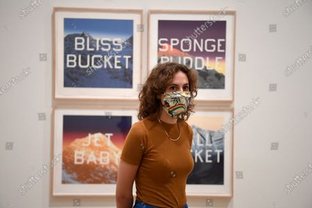 Stock Photo of A masked gallery worker poses by the various works by Edward Ruscha during a media preview of the re-opening of the Tate Modern gallery in London, Britain, 24 July 2020. Tate Modern, Tate Britain, Tate Liverpool and Tate St Ives will be open to visitors from 27 July 2020 with social distancing measures in place.