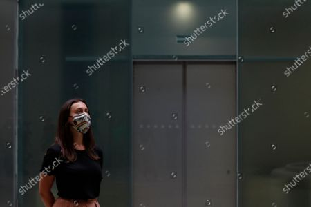Member of staff waits to pose in front of a work of art by Kara Walker entitled Fons Americanus, 2019, at the Tate Modern art museum in London, . The Tate Modern will re-open to the public after closing due to the Coronavirus outbreak on Monday 27 July