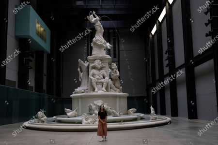 Member of staff poses in front of a work of art by Kara Walker entitled Fons Americanus, 2019, at the Tate Modern art museum in London, . The Tate Modern will re-open to the public after closing due to the Coronavirus outbreak on Monday 27 July