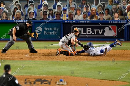 Los Angeles Dodgers' Mookie Betts, right, scores on a fielder's choice hit by Justin Turner as San Francisco Giants catcher Tyler Heineman makes a late tag and home plate umpire Bill Miller makes the call during the seventh inning of an opening day baseball game, in Los Angeles