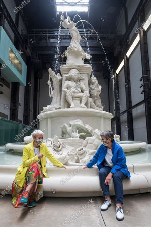"""Maria Balshaw (L), Director Tate, and Frances Morris, Director Tate Modern, wearing facemasks pose next to """"Fons Americanus"""", 2019, by Kara Walker. Press preview ahead of the reopening of Tate Modern on 27 July after the easing of coronavirus pandemic lockdown restrictions by the UK government. Visitors will need to book timed tickets online and follow one-way routes around the gallery space along with observing social distancing rules."""