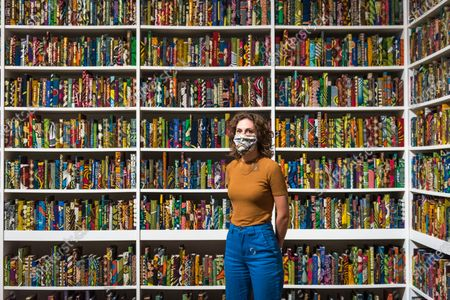"""A Tate staff member wearing a facemask poses next to """"The British Library"""", 2014, Yinka Shonibare CBE. Press preview ahead of the reopening of Tate Modern on 27 July after the easing of coronavirus pandemic lockdown restrictions by the UK government. Visitors will need to book timed tickets online and follow one-way routes around the gallery space along with observing social distancing rules."""