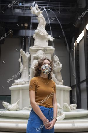 """A Tate staff member wearing a face mask poses next to """"Fons Americanus"""", 2019, by Kara Walker, at the Tate Modern art museum. The Tate Modern will re-open to the public after closing due to the Coronavirus outbreak."""