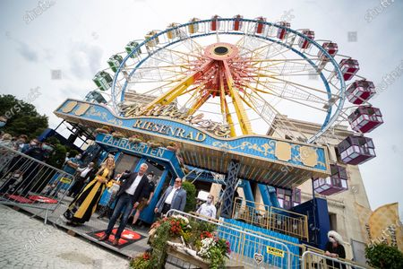 """Mayor of Munich, Dieter Reiter, and the so-called 'Muenchner Kindl' open a ferris wheel with a watering can at the Koenigsplatz in Munich, Bavaria, Germany, 24 July 2020. Under the motto """"Summer in the City"""", rides and cultural offers for residents and visitors will be set up at numerous locations as an alternative to the events cancelled due to the worldwide Coronavirus pandemic."""