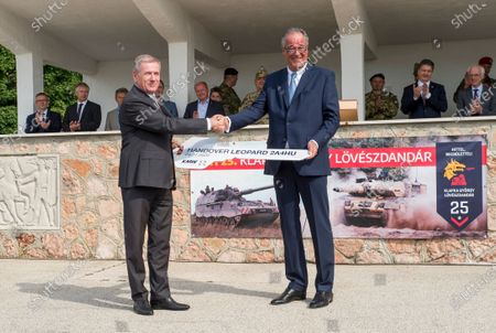 Hungarian Defense Minister Tibor Benko (L) and the CEO of German arms manufacturer Krauss-Maffei Wegmann (KMW), Frank Haun (R), shake hands during the ceremonial delivery of four new Leopard 2A4HU battle tanks to the Hungarian army at a base in Tata, Hungary, 24 July 2020. The Hungarian defense ministry has ordered a total of 12 Leopard tanks from KMW to upgrade its armored fighting vehicles fleet and replace the Soviet-made T72s. Per the deal, the Hungarian military is slated to receive two Leopards per month until the end of the year.