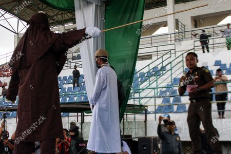 An executioner whips a man for violating the Islamic Sharia law in Lhokseumawe City. The Aceh Islamic Sharia Court dropped 17 lashes on convicted gambling cases after being found guilty. The sentence was carried out in accordance with the Covid-19 health protocol which uses a mask.