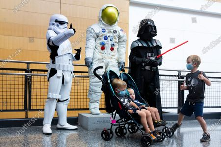 Museum employees dressed as Darth Vader and a Star Wars stormtrooper welcome visitors beside a replica of the NASA space suit worn by Neil Armstrong on Apollo 11, during the reopening of the National Air and Space Museum's Steven F. Udvar-Hazy Center in Chantilly, Virginia, USA, 24 July 2020. The Smithsonian reopened the National Air and Space Museum's Steven F. Udvar-Hazy Center, 24 July, after being closed since mid-March as a public health precaution amidst the coronavirus COVID-19 pandemic. The site reopens allowing twenty percent visitor capacity. The downtown Washington, DC, National Air and Space Museum will remain temporarily closed to the public.