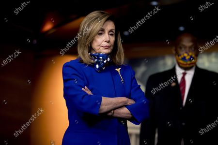 House Speaker Nancy Pelosi of Calif., left, accompanied by Rep. Dwight Evans, D-Pa., right, listens to a question from a reporter during a news conference on Capitol Hill in Washington, on the extension of federal unemployment benefits
